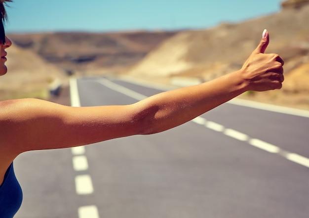 Joven turista caucásico haciendo autostop a lo largo de una carretera en la puesta del sol