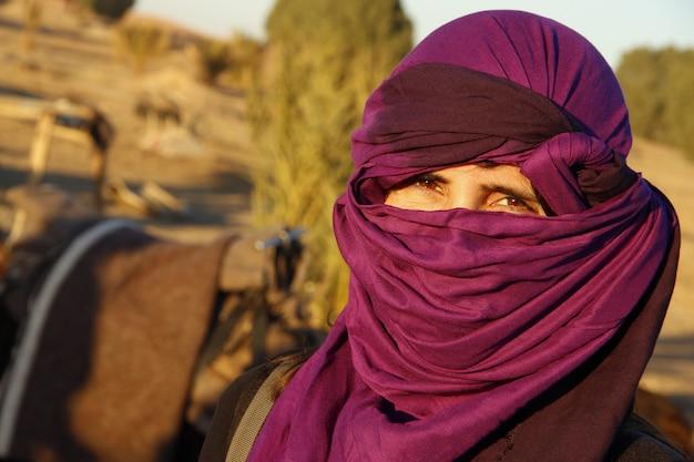 Una joven turista europea con bufanda bereber púrpura en el desierto de merzouga