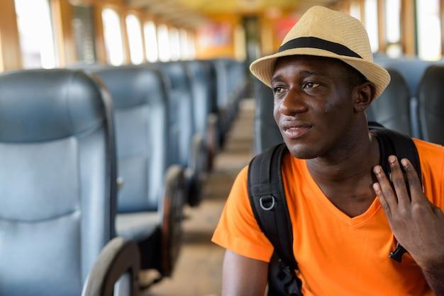 Joven turista feliz hombre sonriendo mientras piensa y mira por la ventana mientras viajaba en el tren