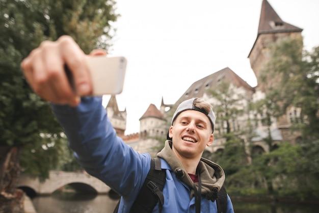 Joven turista feliz toma selfie en edificios históricos y un lago y sonriendo