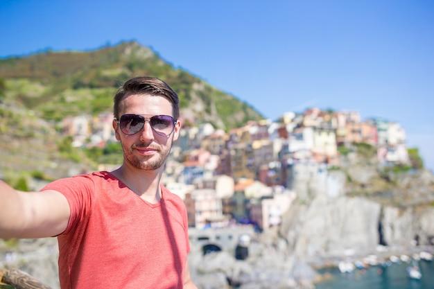 Joven turista en gafas de sol tomando selfie con vista panorámica de manarola, cinque terre, liguria, italia