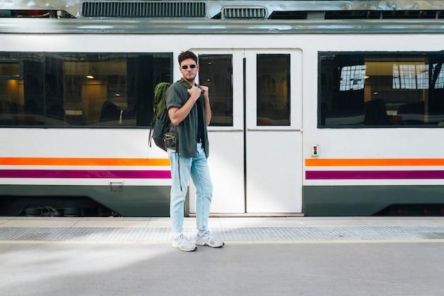 Joven turista masculino con mochila posando en la estación de tren