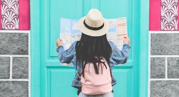 Joven turista mirando el mapa durante el recorrido por la ciudad - chica de viaje recorriendo el casco antiguo de vacaciones - concepto de tendencias de vacaciones, pasión por los viajes y viajes - centrarse en el sombrero