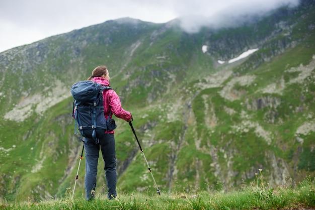 Joven turista con mochila y bastones admirando hermosas montañas rocosas nevadas