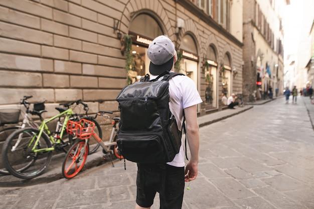 Joven turista con una mochila grande se encuentra en las calles de italia y mira hacia arriba.