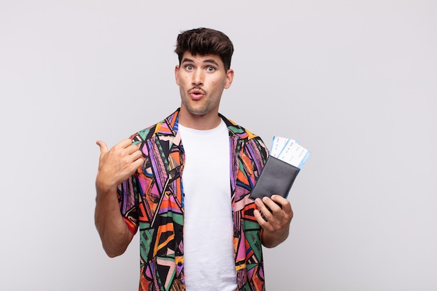 Joven turista con un pasaporte mirando asombrado con incredulidad, señalando un objeto en el costado y diciendo ¡guau, increíble!