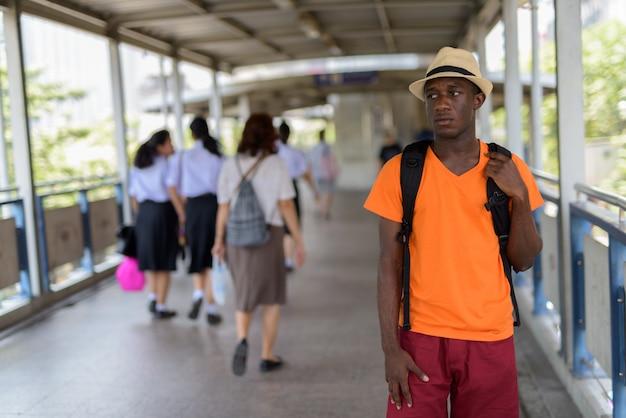 Joven turista de pie y pensando en la pasarela de la estación de metro en bangkok, tailandia