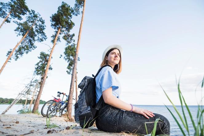 Joven turista sentado cerca del mar