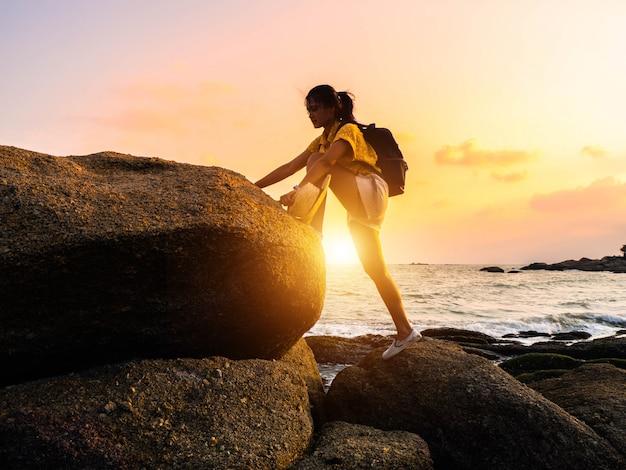 Joven turista está subiendo a la cima de la roca. caminante de la mujer con la mochila sube terreno rocoso escarpado.