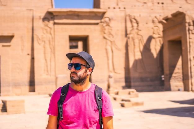 Un joven turista visitando el templo de filae sin gente, una construcción grecorromana, un templo dedicado a isis, diosa del amor. asuán. egipcio