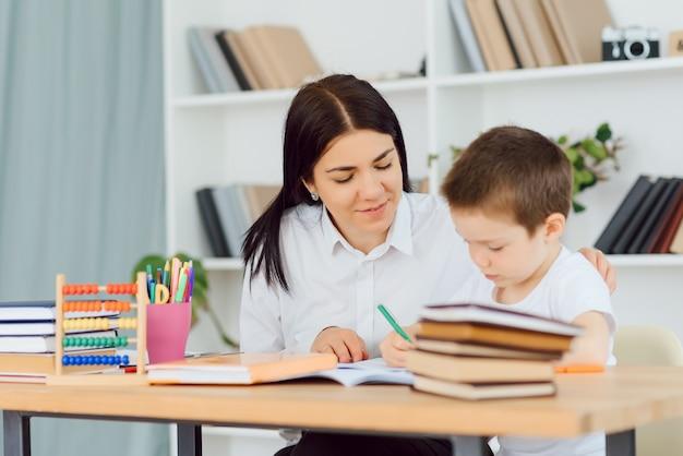 Joven tutor ayudando al pequeño niño de escuela primaria con la tarea durante la lección individual en casa