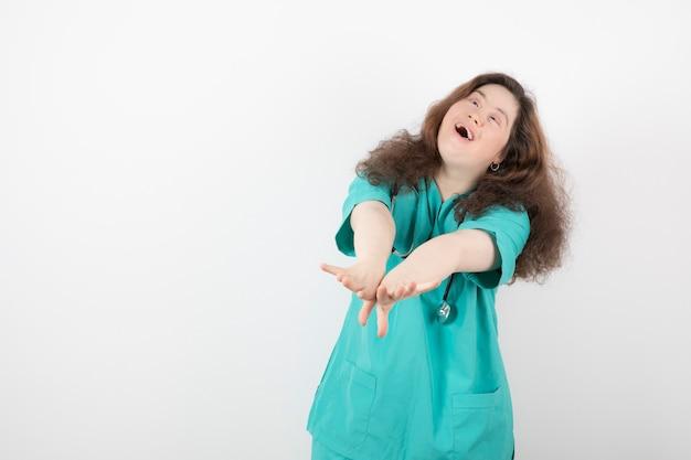 Joven en uniforme verde con estetoscopio de pie y posando.