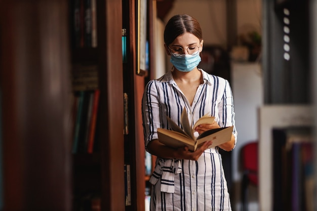 Joven universitaria atractiva con mascarilla de pie en la biblioteca y hojeando material en un libro para el proyecto escolar durante la pandemia del virus corona.
