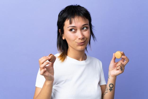 Joven uruguaya sobre púrpura aislado sosteniendo coloridos macarons franceses y pensando