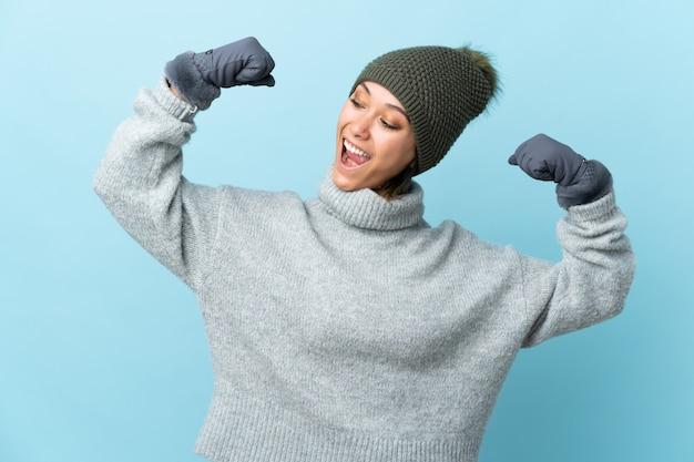 Joven uruguaya con sombrero de invierno en la pared azul celebrando una victoria
