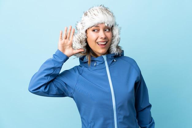 Joven uruguaya con sombrero de invierno en la pared azul escuchando algo