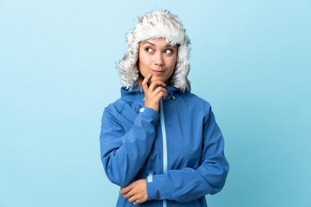 Joven uruguaya con sombrero de invierno en la pared azul pensando una idea