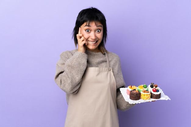 Joven uruguaya sosteniendo muchos mini pasteles diferentes sobre la pared púrpura que tiene dudas y con expresión de la cara confusa