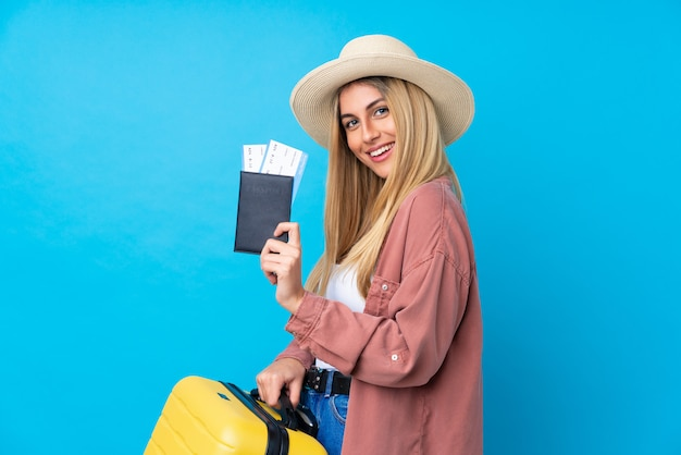 Joven uruguaya en vacaciones con maleta y pasaporte