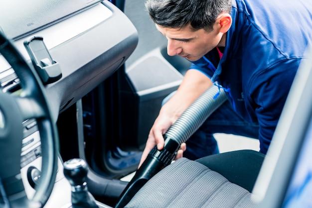 Joven usando aspiradora para limpiar el interior de un auto