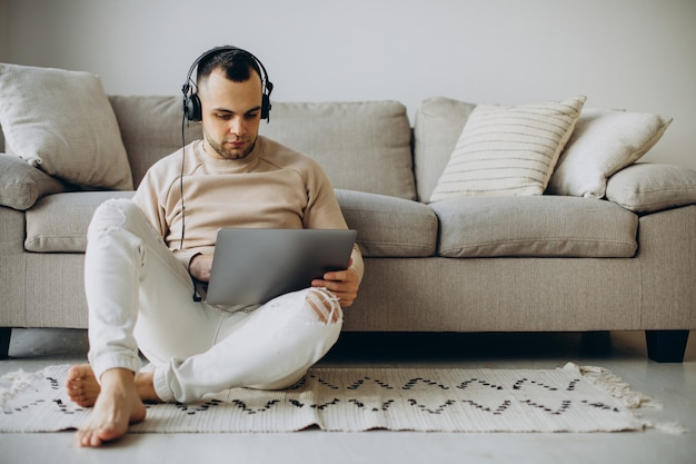 Joven usando audífonos y usando la computadora en casa