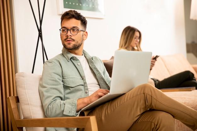 Joven usando laptop mientras está sentado con una mujer joven en casa