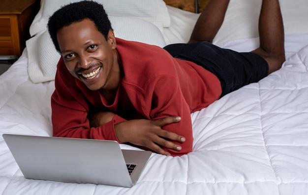 Joven usando su computadora portátil en la cama