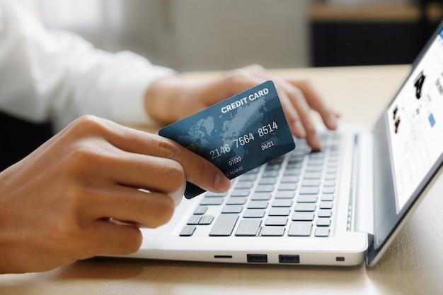 Joven usando una tarjeta de crédito para compras en línea