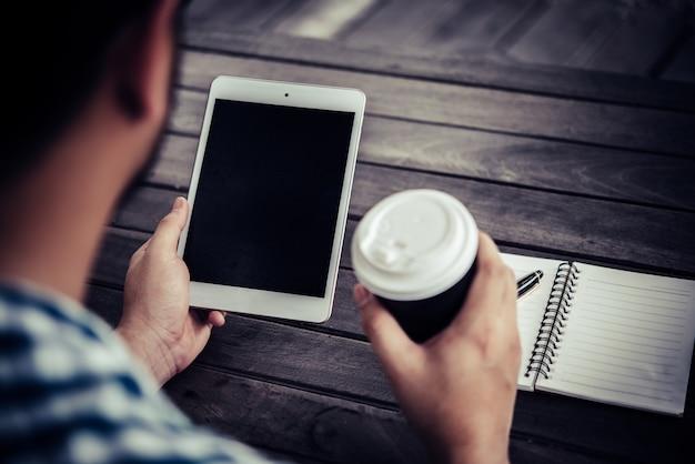 Joven utilizando tableta digital mientras bebe café sentado en el jardín de la casa, relajante por la mañana.