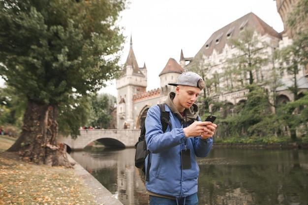 Joven está utilizando un teléfono inteligente en el castillo de vajdahunyad en budapest, hungría