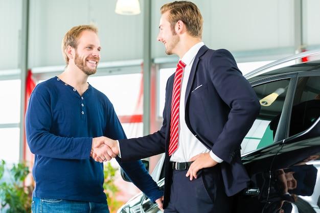 Joven y vendedor con auto en concesionario de automóviles