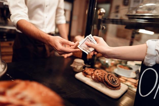 Joven vendiendo pan al cliente en panadería