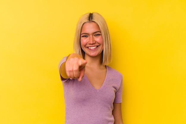 Joven venezolana aislada en la pared amarilla apuntando al frente con los dedos.