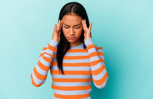 Joven venezolana aislada sobre fondo azul tocando templos y teniendo dolor de cabeza.