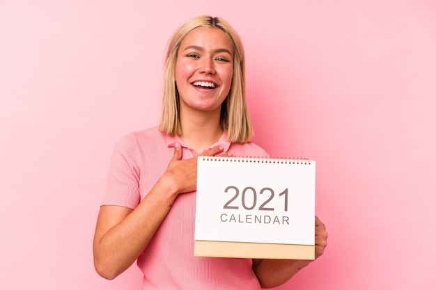 Joven venezolana sosteniendo un calendario 2021 aislado en la pared rosa se ríe a carcajadas manteniendo la mano en el pecho.