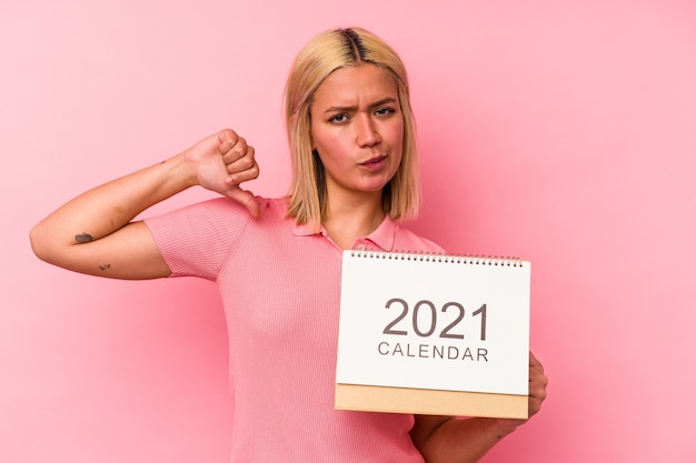Joven venezolana sosteniendo un calendario 2021 aislado en una pared rosa se siente orgullosa y segura de sí misma, ejemplo a seguir.