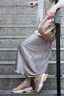 Joven vestida con estilo en zapatillas de deporte y con una mochila en el hombro se encuentra en las escaleras apoyándose en la barandilla