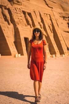 Una joven vestida de rojo visitando el templo egipcio de nefertari cerca de abu simbel en el sur de egipto en nubia junto al lago nasser. templo del faraón ramsés ii, estilo de vida de viaje