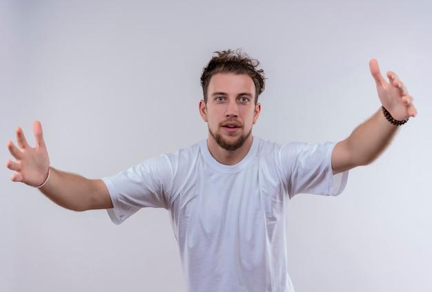 Joven vestido con camiseta blanca que muestra el tamaño en la pared blanca aislada