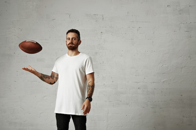 Joven vestido con una camiseta sin mangas de algodón blanco en blanco y jeans negros lanzando un fútbol vintage marrón aislado en blanco