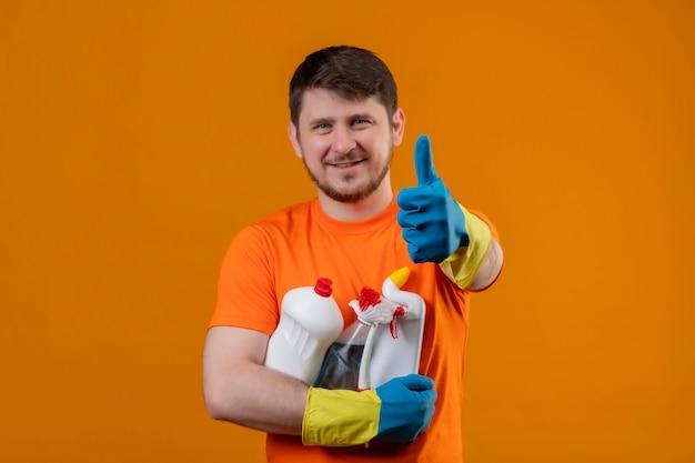 Joven vestido con camiseta naranja y guantes de goma con suministros de limpieza sonriendo alegremente positivo y feliz mirando a la cámara mostrando los pulgares para arriba listo para limpiar el concepto sobre fondo naranja