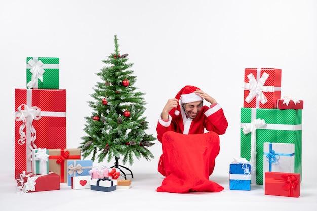 Joven vestido como papá noel con regalos y árbol de navidad decorado sentado en el suelo poniendo ambas manos