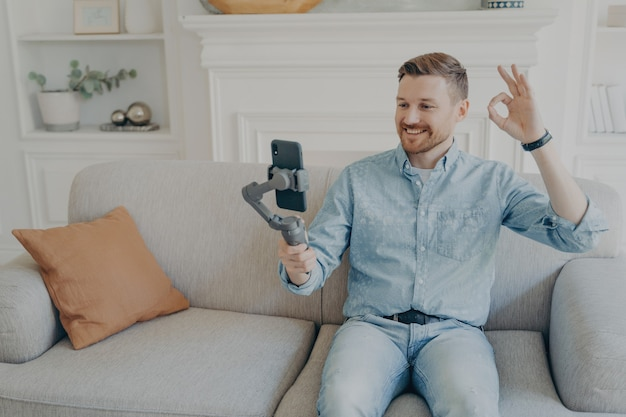 Joven vestido de manera informal mostrando los pulgares hacia arriba mientras habla por video usando el teléfono conectado al cardán, sentado cómodamente en el sofá beige en la sala de estar, conversando con la familia