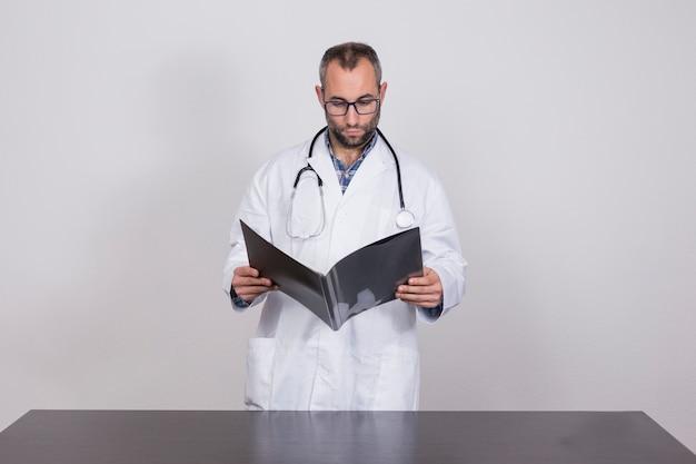 Joven veterinario con estetoscopio y tapa blanca leyendo documentos