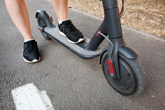 La joven viaja en el scooter eléctrico por la ciudad de la tarde por los senderos.