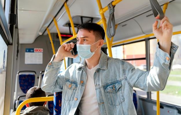 Joven viajando en autobús urbano con smartphone
