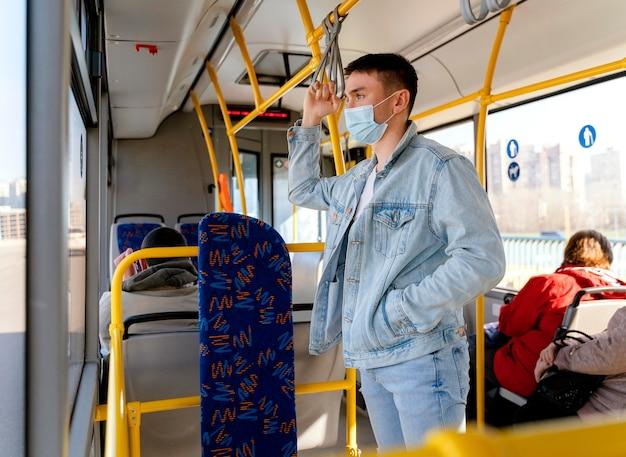 Joven viajando en autobús urbano vistiendo mascarilla quirúrgica