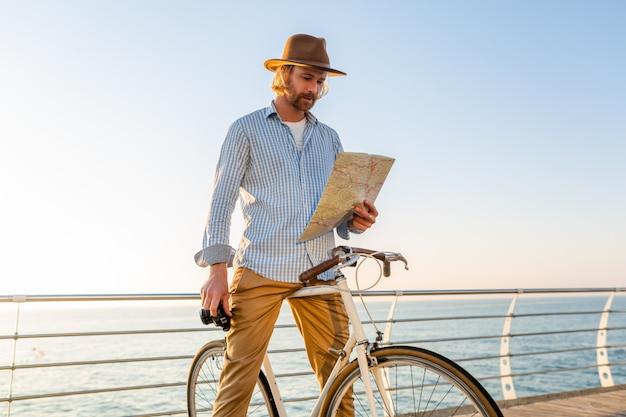 Joven viajando en bicicleta por mar en vacaciones de verano al atardecer, sosteniendo el mapa de turismo y la cámara