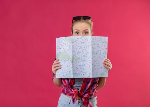Joven viajera con camisa roja y gafas en la cabeza cubrió la boca con el mapa en la pared rosa aislada