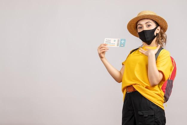 Joven viajera con mochila vistiendo máscara negra sosteniendo boleto de viaje en blanco